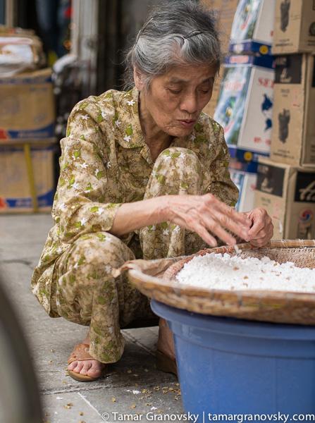 Hanoi (woman sorting through rice)