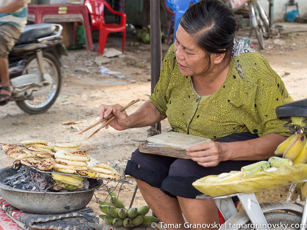 Mekong Delta (woman roasting glutinous rice covered bananas)